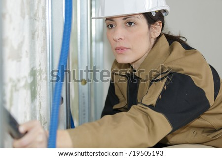female electrician installing ventilation in ceiling