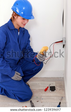 Female electrician taking electrical reading