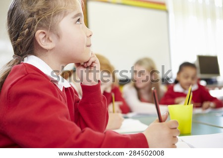 Female Elementary Pupil Working At Desk - stock photo