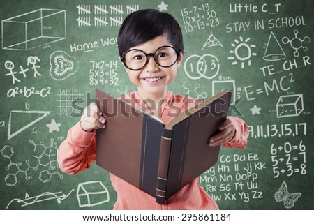 Female elementary school standing in the class while holding a textbook and smiling on the camera near the blackboard - stock photo