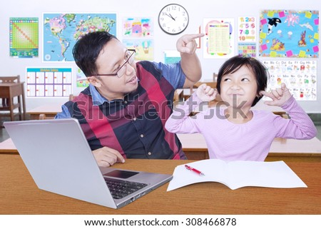 Female elementary school student closing her ears when get advice from her teacher in the classroom - stock photo