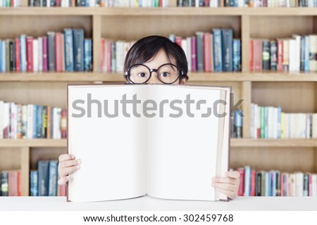 Female elementary school student sitting in the library while wearing glasses and showing empty book - stock photo