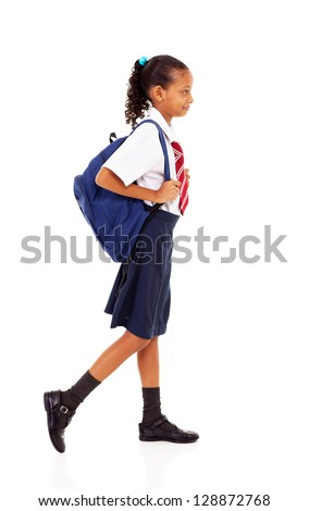 female elementary school student walking on white - stock photo
