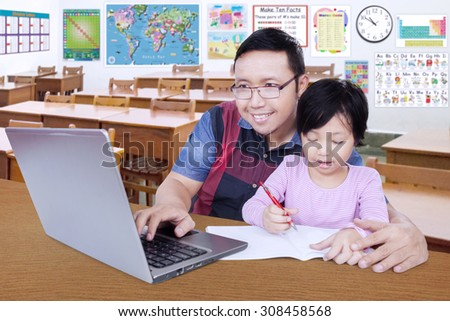 Female elementary school student write on the book in the classroom while her teacher using laptop - stock photo