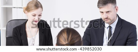 Female employee is sitting in front of her managers who are listening her carefully