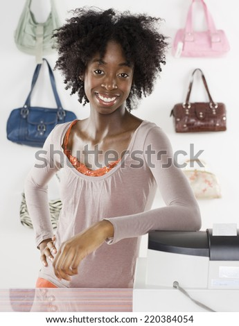 Female employee smiling from behind the counter - stock photo
