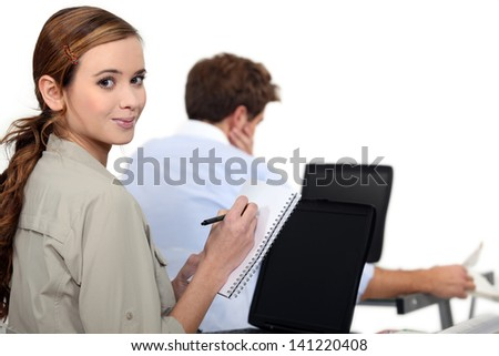 female employee writing notes near a colleague - stock photo