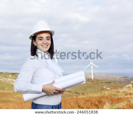 Female engineer holding blueprints at wind turbine site - stock photo