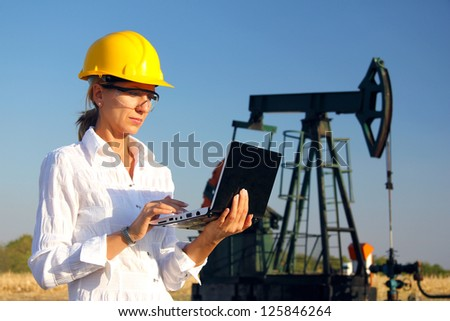 Female engineer in an oilfield working with notebook - stock photo