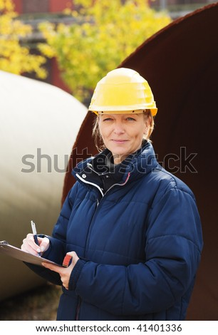 Female engineer in yellow hard hat taking notes at construction site - stock photo