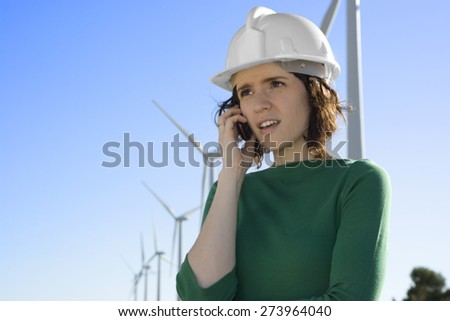 Female Engineer Talking on Cell Phone in Front of Modern Wind Turbines - stock photo