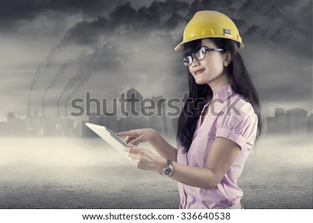 Female engineer using digital tablet outdoors. shoot under air pollution - stock photo