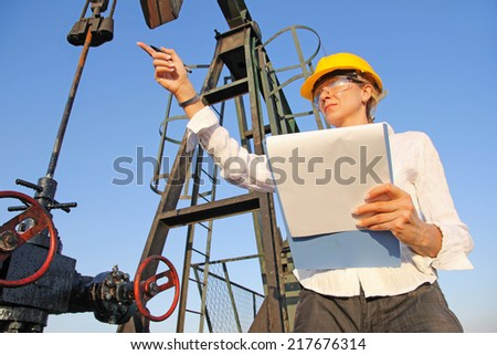 Female engineer writing on clipboard in oil field. She showing by hand what needs to be fixed