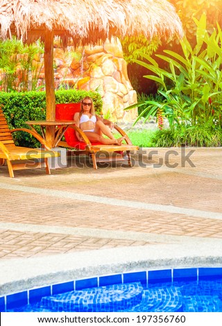 Female enjoying summer holidays, woman on day spa relaxation, sexy girl sunbathing near pool, luxury vacation on tropical resort, travel the world concept - stock photo