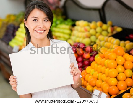 Female entrepreneur holding a banner at the supermarket - stock photo