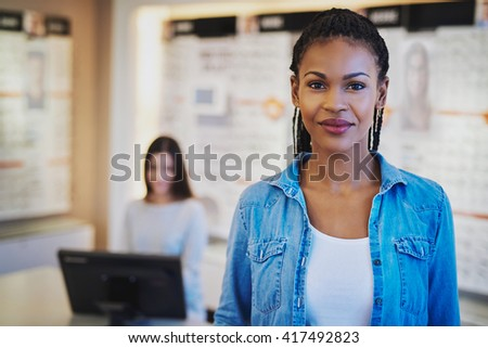 Female entrepreneur in her shop with colleague in background