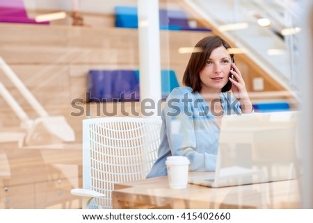 Female entrepreneur talking on her phone in modern office - stock photo