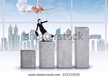 Female entrepreneur tied on ropes and walk on business graph with controlled by someone - stock photo