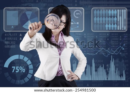 Female entrepreneur using a magnifier to monitoring her business in front of financial background - stock photo