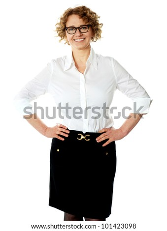 Female executive posing with hands on her waist, smiling at camera