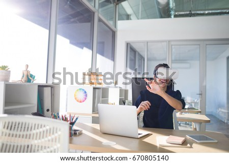 Female executive using virtual reality headset at her desk in office