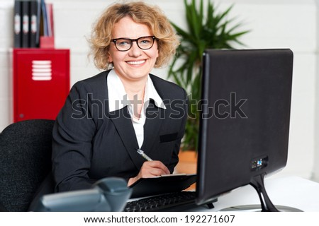 Female executive writing notes on clipboard looking at you