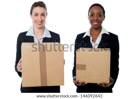 Female executives holding cardboard boxes