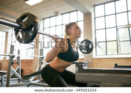 Female exercising in gym doing squats with extra weight on her shoulders. Young woman working out with heavy weights in a fitness club. - stock photo