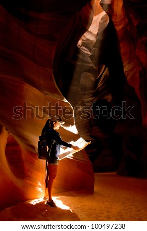Female explorer inside a cave at the Grand Canyon - stock photo
