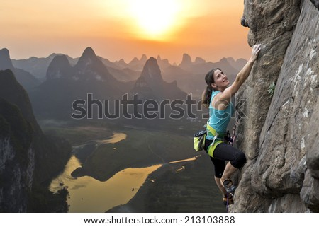 Female extreme climber conquers steep rock against the sunset over the river. China, typical Chinese landscape with mountains and river. - stock photo