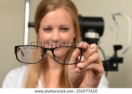 Female eye doctor holding glasses - focus on glasses - stock photo