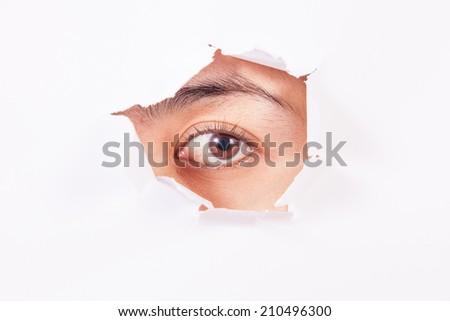 Female eye looking through hole - stock photo