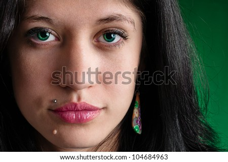 Female face highly detailed close up on green background