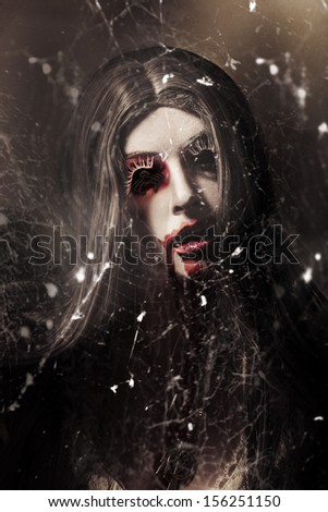 Female face of dark horror lurking in the shadows of darkness beneath the spin of spider webs. Eye of the black widow - stock photo