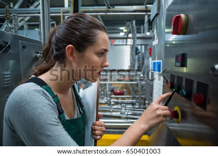 Female factory worker operating machine in bottle factory