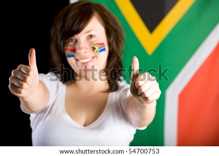 female fan of south africa, thumbs up, also small flags painted on her cheeks