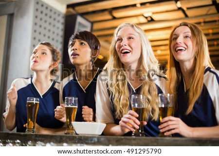 Female fan watching football at bar counter in bar