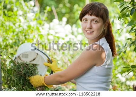 Female farmer composting grass in garden - stock photo