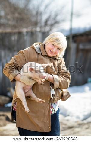 Female farmer holding a pig.Domestic animal breeding - stock photo