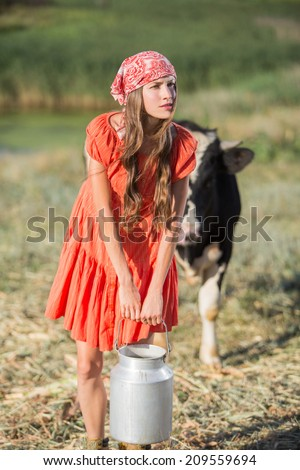 Female farmer is working on the organic farm with dairy cows and holding big milk container pot - stock photo