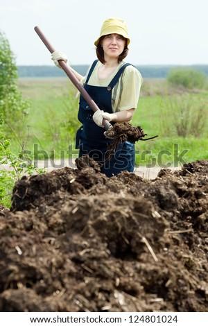 Female farmer spreads manure at field - stock photo