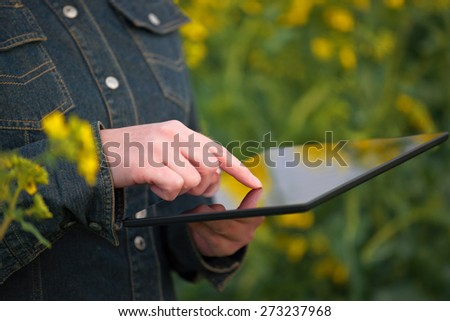 Female Farmer using Digital Tablet Computer in Oilseed Rapeseed Cultivated Agricultural Field Examining and Controlling The Growth of Plants - stock photo