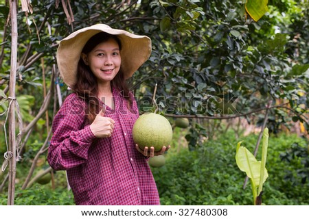 Female farmer with her pomelo farm. - stock photo