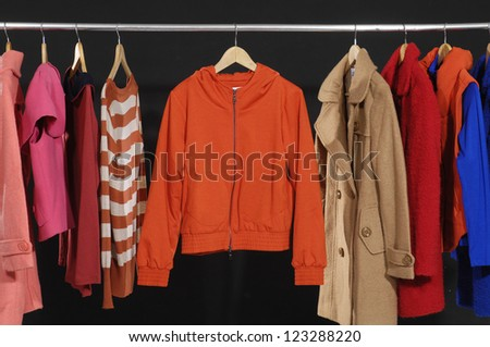 female fashion clothing on hangers at the show-black background
