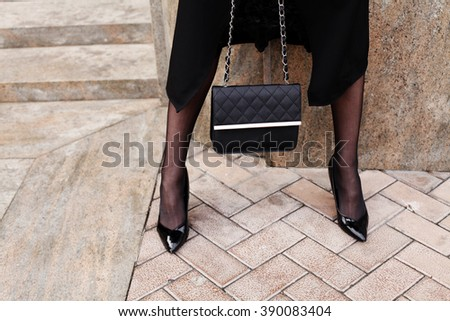 Female fashion concept. Close up. Detail of black high heels and leather bag. Street style, black outfit