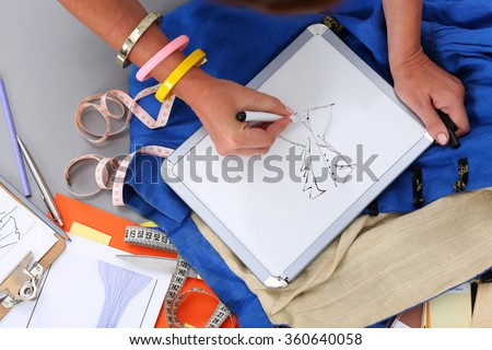 Female fashion designer hands holding drawing pad and pen making sketch of new dress. Style and design development and creating garment, clothes sew and repair service, seamstress at work concept - stock photo