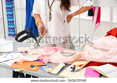 Female fashion designer holding big golden tailor scissors in hand closeup. Creating garment, dress sewing service, seamstress ready to take measurement and make new suit concept - stock photo