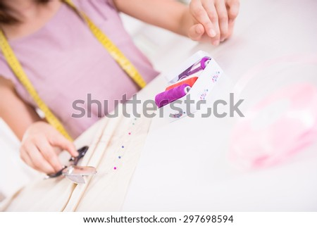 Female fashion designer sitting in her office and working, close-up.