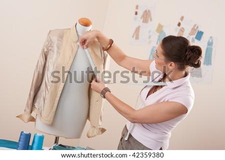 Female fashion designer taking measurement of jacket at studio - stock photo