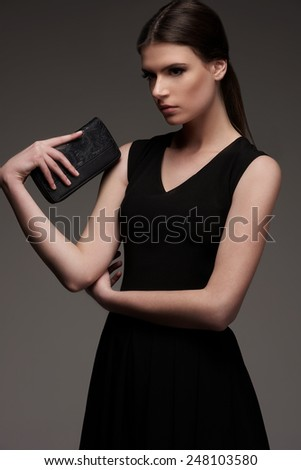 Female fashion model in black dress with clutch stay on gray background